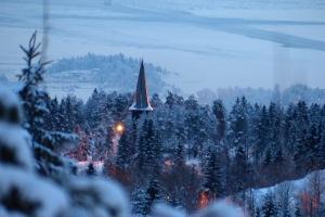 Die Holmenkollen-Kirche im abendlichen Winterkleid mit Fjord im Hintergrund...