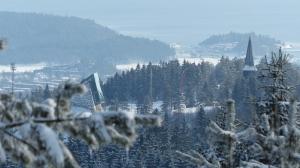 Blick vom Frognersettern zur kleinen Schanze (Glas-Stein-Bau links) Holmenkollen-Kirchturm rechts, TV-Kameras in Luftiger Höhe (Roter Liftarm) und Bygdøy-Halbinsel mit Yachthafen im Hintergrund