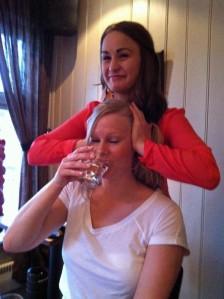 Praxistip's auf dem Sommerfest: erfolgreiche Bekämpfung von Schluckauf: Inger-Marie hält Eva-Katherine die Ohren zu und sie muss gleichzeitig ein Glas Wasser trinken